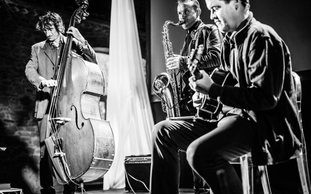 Le groupe de musique en trio (saxophoniste, guitariste et contrebassiste lors de l'animation musicale d'un mariage à Arles - 13200
